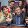 Happy man surrounded by women at roulette table — Stock Photo #23092046