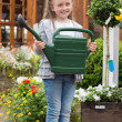 Little girl holding watering can while smiling — Stock Photo #23092250