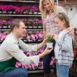 Employee giving a flower to little girl in garden center — Stock Photo #23092544