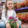 Little girl sitting on the path with a flower — Stock Photo #23092580