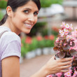 Womsmiling while holding flower — Stock Photo #23092852