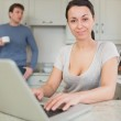 Young woman using laptop with man drinking coffee — Stock Photo
