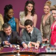 Men playing roulette as women are watching — Foto de Stock