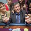 Women surrounding man at roulette table - Stockfoto