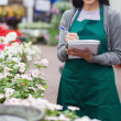 Garden center worker taking notes and smiling — Stock Photo