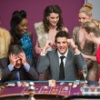 Stock Photo: Man winning as another is losing at roulette table