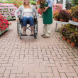 Garden center employee and woman in wheelchair — Stock Photo