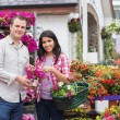 Happy couple shopping for flowers — Stock Photo