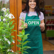 Woman holding open sign at entrance to garden center - Foto Stock