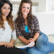 Two women sitting on a couch while writing on a notepad — Stock Photo