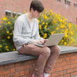 Stock Photo: Student using laptop outside