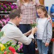 Little girl getting a present from garden center worker — Stock Photo #23093846
