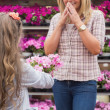 Child presenting flowers to her mother in garden center — Stock Photo
