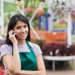 Woman working in garden center making a call - Stock Photo