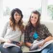 Two happy girls with their homework — Stockfoto