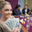 Stock Photo: Blonde woman holding fan of dollars