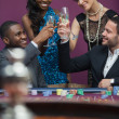Clinking glasses at roulette table — Stock Photo