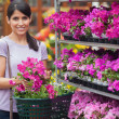 Woman smiling and carrying a basket of flowers — Stock Photo
