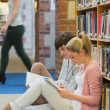 Boy and girl sitting on floor of library studying — Stock Photo
