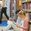 Boy and girl sitting on floor of library studying — Stock Photo #23098482