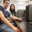 Man and woman sitting at computer desk — Stock Photo