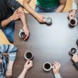 Sitting around table drinking coffee — Stock Photo #23098652