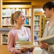 Stock Photo: Couple smiling at each other at library