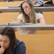 Students sitting at the lecture hall writing — Stock Photo