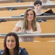 Students sitting smiling in lecture hall — Stock Photo #23099116