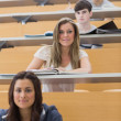Students sitting smiling in lecture hall — Stock Photo