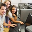 Students sitting at the computer room smiling — Stock Photo #23099300