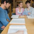 Students sitting at library table smiling while holding a tablet — Stock Photo