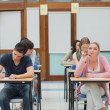 Stock Photo: Students in an exam while one is thinking