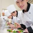 Smiling chef preparing salad in culinary class - Stock Photo