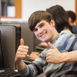 Man sitting at computer giving thumbs up - Stock fotografie