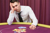 Man looking worried at poker table — Stock Photo