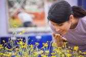 Woman smelling yellow flowers happily — Stock Photo