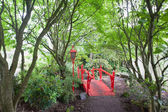 Red Japanese style bridge in forest — Stock Photo