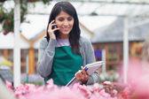 Garden center worker phoning while taking notes — Stock Photo