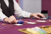 Dealer distributing cards at table — Stock Photo