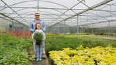 Gardener and granddaughter holding a large potted plant — Foto Stock