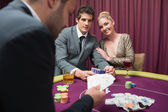 Couple playing poker and smiling — Stock Photo