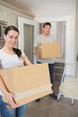 Young couple holding moving boxes — Stock Photo