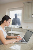 Woman using laptop with robber looking at her through window — Stock Photo