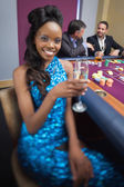 Woman at roulette table holding champagne glass — Stock Photo