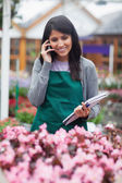 Black-haired woman calling while doing stocktaking — Stock Photo