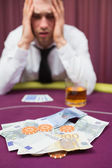 Man betting cash at poker game — Stockfoto