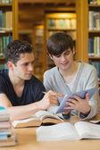 студент, показывая другой что-то на планшете в библиотеке — Стоковое фото