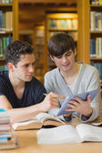 Student showing another something on tablet in library — Stock Photo