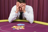 Man holding head in hands at poker table — Stock Photo